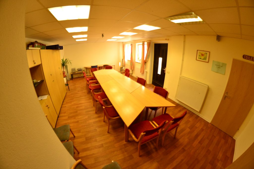 Ein Gruppenraum mit Schränken, aneinander gereihten Tischen und Stühlen sowie einer Tür zum Innenhof.