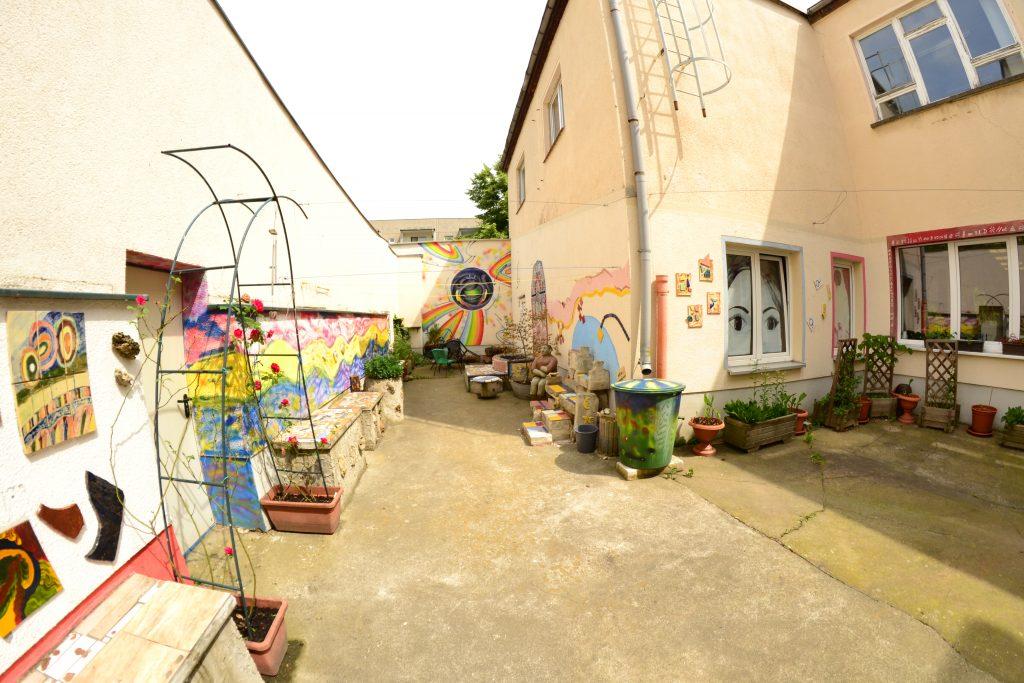 Ein Innenhof mit bunt bemalten Wänden und Fenstern. Am Rand stehen Blumenkästen und Sitzbänke.