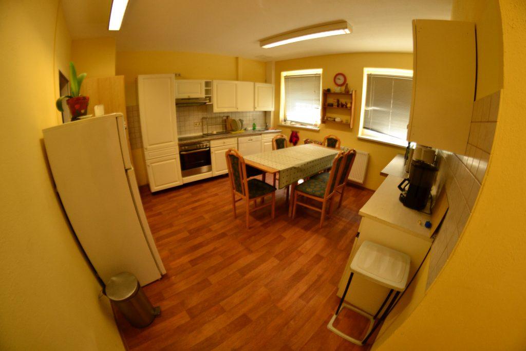 Eine Küche mit einem Tisch und Stühlen in der Mitte.