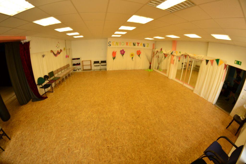 Ein großer Tanzraum mit einer Spiegelwand.