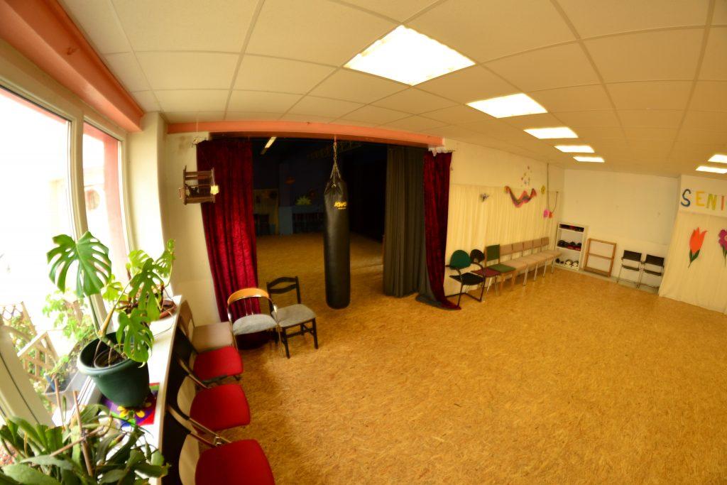 Ein Tanzraum mit einer Spiegelwand. Blick durch einen Vorhang zum hinteren Teil der Tanzscheune. In der Mitte hängt ein Boxsack.