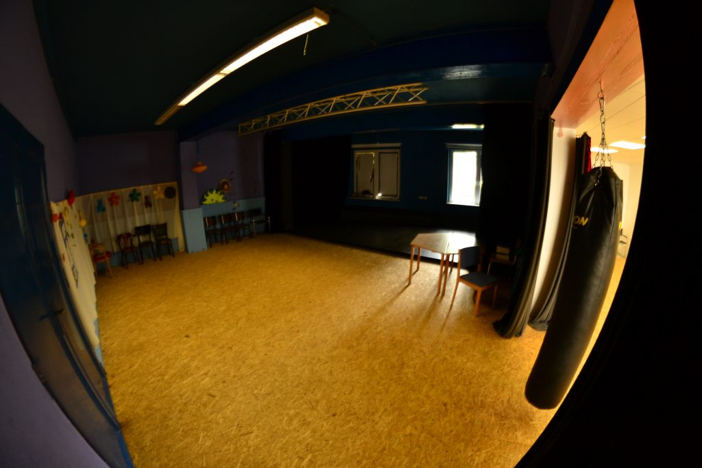 Ein dunkelblau gestrichener Raum mit Stühlen am Rand.