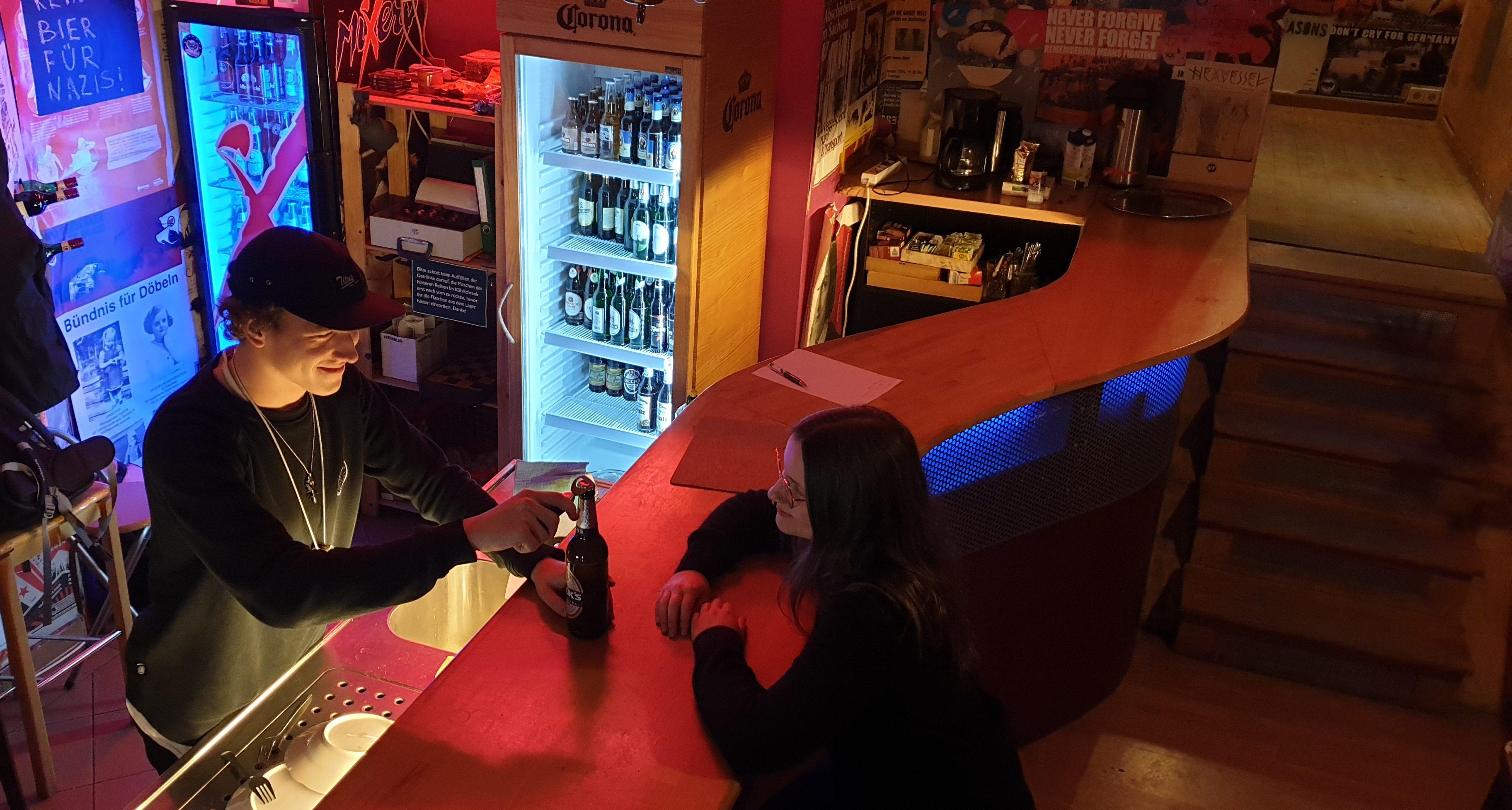 Eine Bar, an der ein Ehrenamtlicher einem Gast ein Getränk ausschenkt.