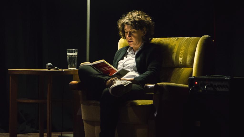 Eine Referentin sitzt in einem Sessel auf der Bühne des Café Courage und liest aus einem Buch vor.