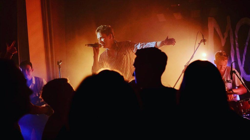 Ein Sänger auf der Bühne des Café Courage während eines Konzerts. Von den Zuschauer*innen vor ihm sind nur die Silhouetten zu sehen.