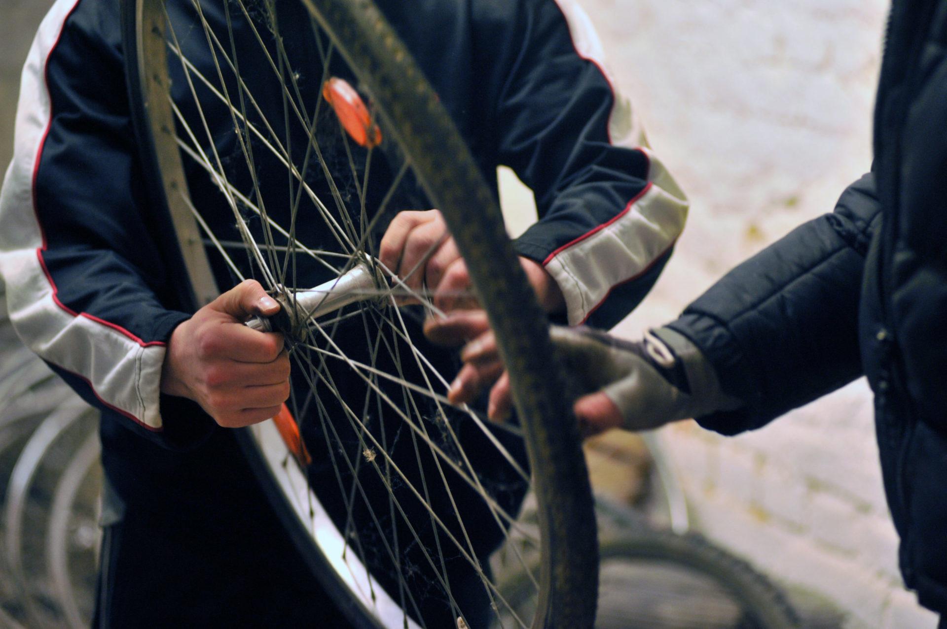 Hände von zwei Personen bei der Fahrradreparatur.