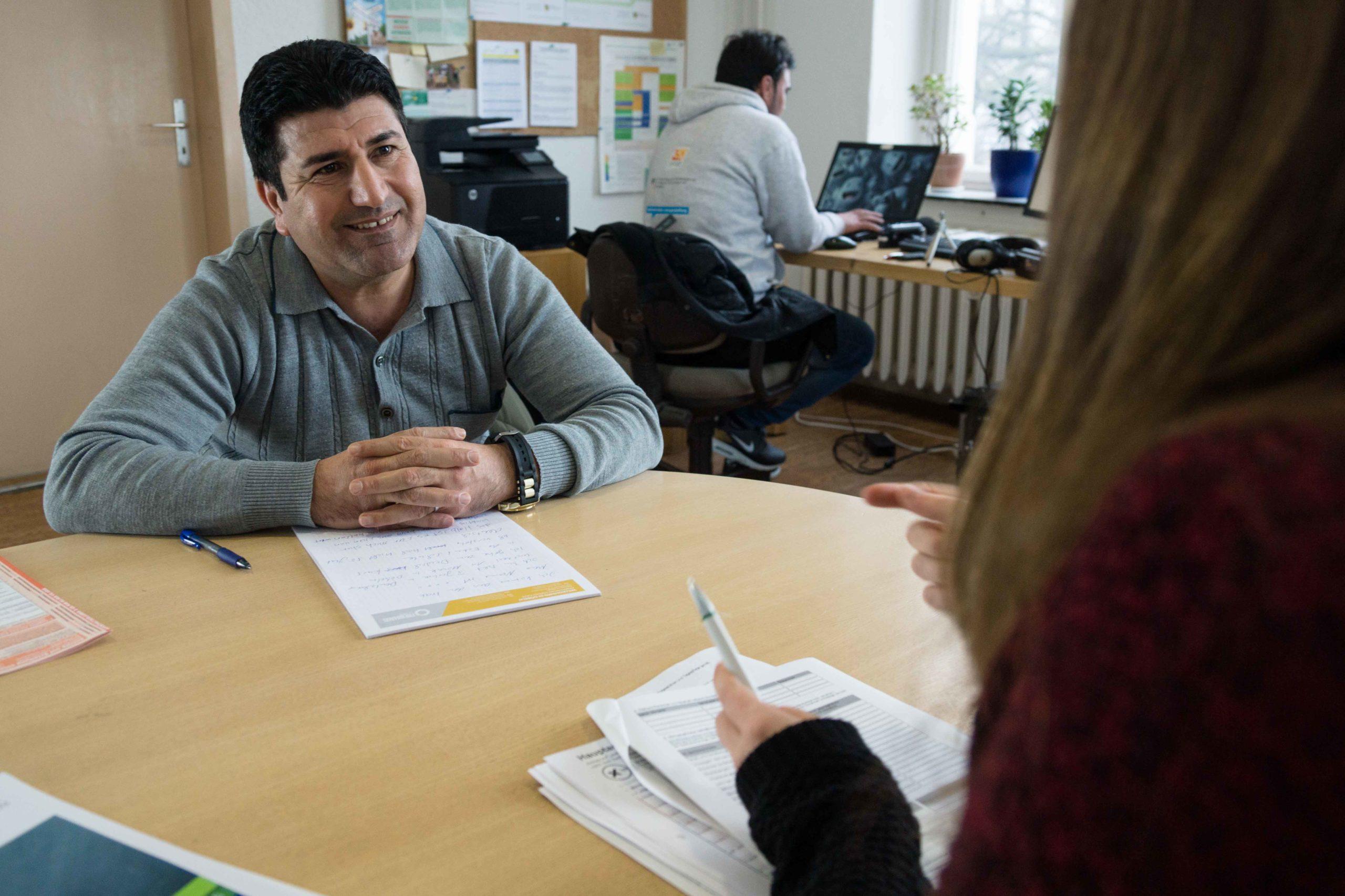 Eine Ehrenamtliche berät einen Mann beim Ausfüllen von Formularen. Im Hintergrund ein weiterer Mann an einem Computer sitzend.
